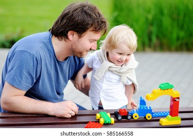 Middle age father with his toddler son playing with colorful plastic blocks. Family leisure concept