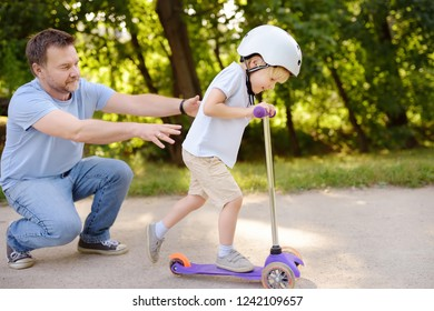 Middle age father showing his toddler son how to ride a scooter in summer park. Active family leisure. Child in helmet. Safety, sports, leisure with kids concept.