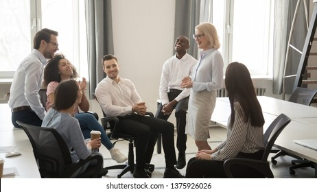 Middle age female leader coach and corporate team young specialists resting having pause during training, laughing friendly office employees and mature lady boss enjoy fun conversation at coffee break