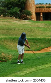 Middle age golfer hitting the ball onto the green. Halfway house in the background. Golf club is in motion.