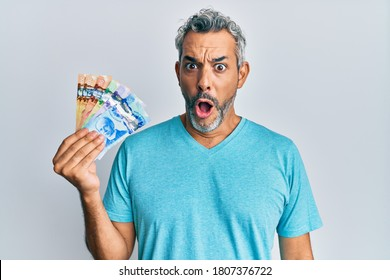 Middle age grey-haired man holding canadian dollars scared and amazed with open mouth for surprise, disbelief face