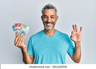 Middle age grey-haired man holding australian dollars doing ok sign with fingers, smiling friendly gesturing excellent symbol