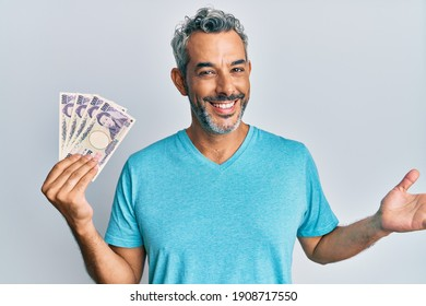 Middle age grey-haired man holding japanese yen banknotes celebrating achievement with happy smile and winner expression with raised hand
