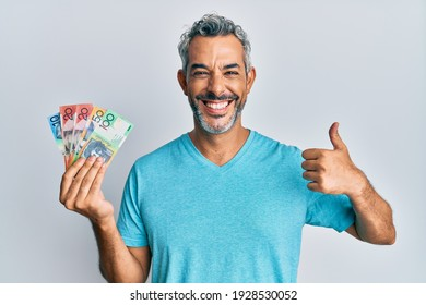 Middle age grey-haired man holding australian dollars smiling happy and positive, thumb up doing excellent and approval sign