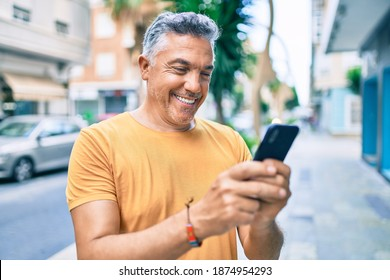 Middle age grey-haired man smiling happy using smartphone walking at street of city.