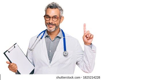 Middle age grey-haired man wearing doctor stethoscope holding clipboard surprised with an idea or question pointing finger with happy face, number one