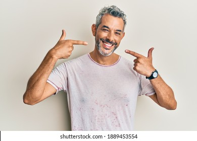 Middle age grey-haired man wearing casual clothes smiling cheerful showing and pointing with fingers teeth and mouth. dental health concept.