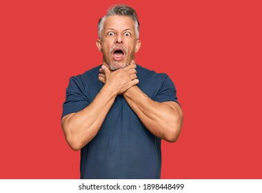 Middle age grey-haired man wearing casual clothes shouting and suffocate because painful strangle. health problem. asphyxiate and suicide concept.