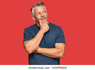 Middle age grey-haired man wearing casual clothes with hand on chin thinking about question, pensive expression. smiling with thoughtful face. doubt concept.