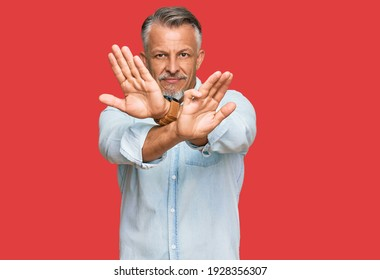 Middle age grey-haired man wearing casual clothes rejection expression crossing arms and palms doing negative sign, angry face