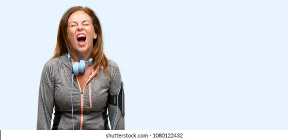 Middle age gym fit woman with workout headphones stressful, terrified in panic, shouting exasperated and frustrated. Unpleasant gesture. Annoying work drives me crazy isolated blue background