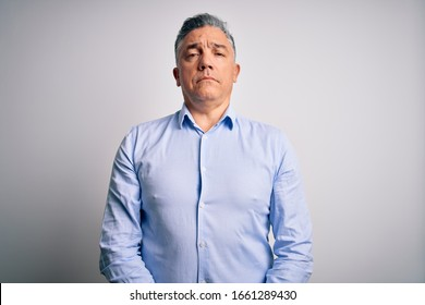 Middle age handsome grey-haired business man wearing elegant shirt over white background Relaxed with serious expression on face. Simple and natural looking at the camera.