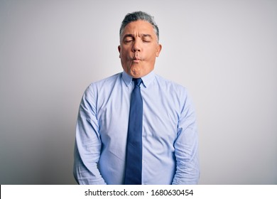 Middle age handsome grey-haired business man wearing elegant shirt and tie making fish face with lips, crazy and comical gesture. Funny expression.