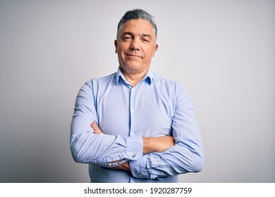 Middle age handsome grey-haired business man wearing elegant shirt over white background happy face smiling with crossed arms looking at the camera. Positive person.