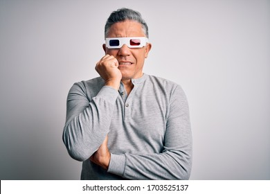 Middle age handsome grey-haired man using 3d glasses over isolated white background looking stressed and nervous with hands on mouth biting nails. Anxiety problem.
