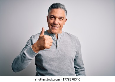 Middle age handsome grey-haired man wearing casual t-shirt over white background doing happy thumbs up gesture with hand. Approving expression looking at the camera showing success.