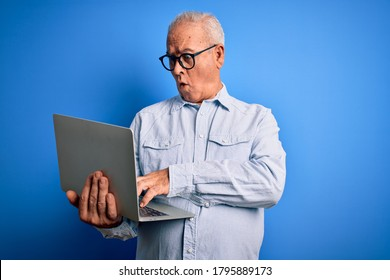 Middle age handsome hoary business man wearing glasses working using laptop scared in shock with a surprise face, afraid and excited with fear expression