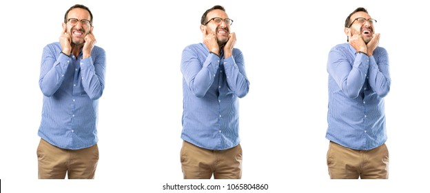 Middle age handsome man covering ears ignoring annoying loud noise, plugs ears to avoid hearing sound. Noisy music is a problem. over white background