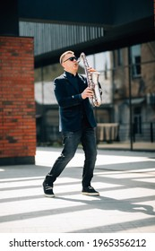 Middle age handsome man playing saxophone outdoors