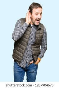 Middle age handsome man wearing winter vest smiling with hand over ear listening an hearing to rumor or gossip. Deafness concept.