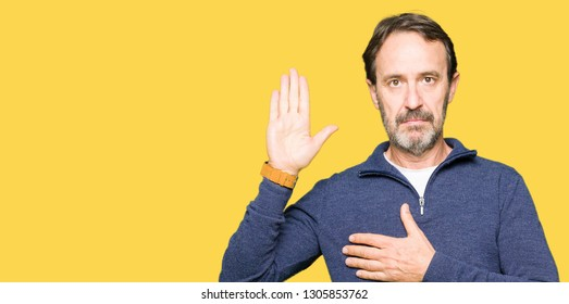 Middle age handsome man wearing a sweater Swearing with hand on chest and open palm, making a loyalty promise oath