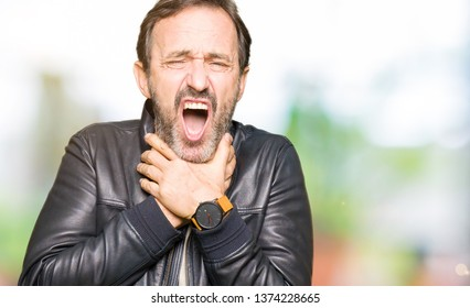 Middle age handsome man wearing black leather jacket shouting and suffocate because painful strangle. Health problem. Asphyxiate and suicide concept.