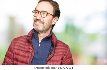 Middle age handsome man wearing glasses and winter coat smiling looking side and staring away thinking.