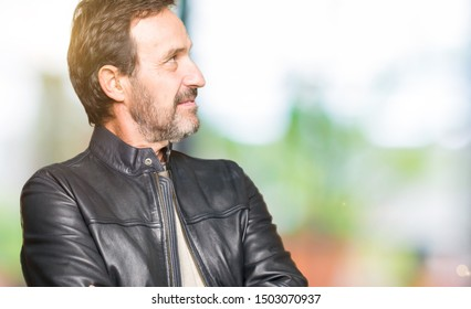 Middle age handsome man wearing black leather jacket smiling looking to the side with arms crossed convinced and confident