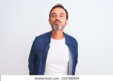 Middle age handsome man wearing blue denim shirt standing over isolated white background looking at the camera blowing a kiss on air being lovely and sexy. Love expression.