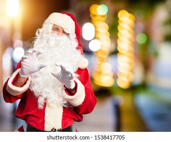 Middle age handsome man wearing Santa Claus costume and beard standing disgusted expression, displeased and fearful doing disgust face because aversion reaction. With hands raised. Annoying concept.