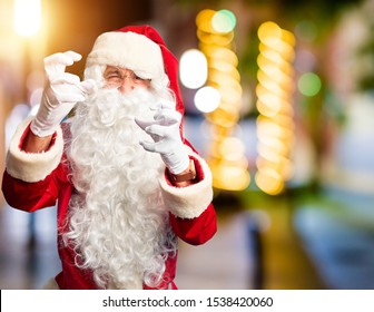 Middle age handsome man wearing Santa Claus costume and beard standing Shouting frustrated with rage, hands trying to strangle, yelling mad