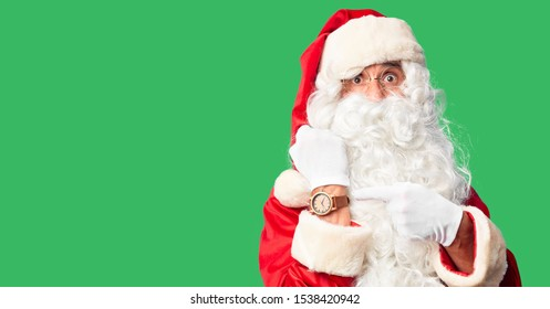 Middle age handsome man wearing Santa Claus costume and beard standing In hurry pointing to watch time, impatience, looking at the camera with relaxed expression