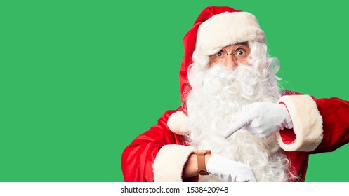 Middle age handsome man wearing Santa Claus costume and beard standing In hurry pointing to watch time, impatience, upset and angry for deadline delay
