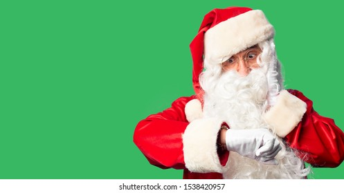 Middle age handsome man wearing Santa Claus costume and beard standing Looking at the watch time worried, afraid of getting late