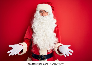 Middle age handsome man wearing Santa costume standing over isolated red background smiling cheerful with open arms as friendly welcome, positive and confident greetings