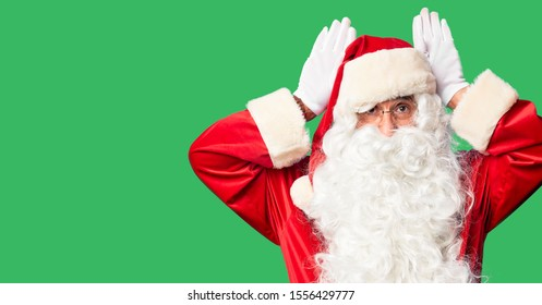 Middle age handsome man wearing Santa Claus costume and beard standing Doing bunny ears gesture with hands palms looking cynical and skeptical. Easter rabbit concept.