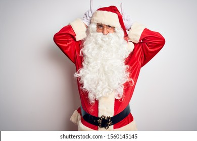 Middle age handsome man wearing Santa costume standing over isolated white background Posing funny and crazy with fingers on head as bunny ears, smiling cheerful