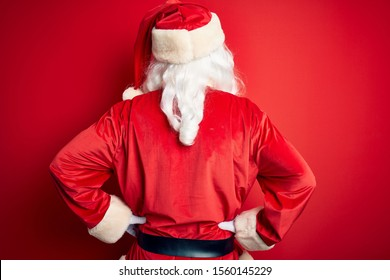 Middle age handsome man wearing Santa costume standing over isolated red background standing backwards looking away with arms on body