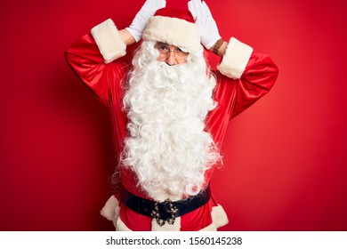 Middle age handsome man wearing Santa costume standing over isolated red background Doing bunny ears gesture with hands palms looking cynical and skeptical. Easter rabbit concept.
