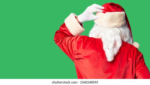 Middle age handsome man wearing Santa Claus costume and beard standing Backwards thinking about doubt with hand on head