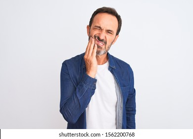 Middle age handsome man wearing blue denim shirt standing over isolated white background touching mouth with hand with painful expression because of toothache or dental illness on teeth. Dentist