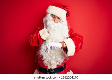 Middle age handsome man wearing Santa costume standing over isolated red background Looking at the watch time worried, afraid of getting late