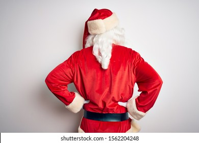 Middle age handsome man wearing Santa costume standing over isolated white background standing backwards looking away with arms on body