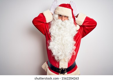 Middle age handsome man wearing Santa costume standing over isolated white background Doing bunny ears gesture with hands palms looking cynical and skeptical. Easter rabbit concept.