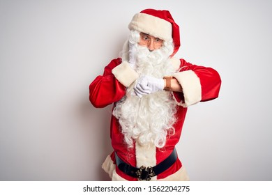 Middle age handsome man wearing Santa costume standing over isolated white background Looking at the watch time worried, afraid of getting late