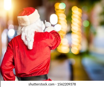 Middle age handsome man wearing Santa Claus costume and beard standing Posing backwards pointing ahead with finger hand