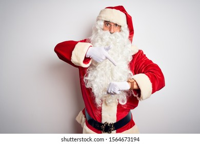 Middle age handsome man wearing Santa costume standing over isolated white background In hurry pointing to watch time, impatience, upset and angry for deadline delay