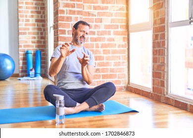 Middle age handsome sportman sitting on mat doing stretching yoga exercise at gym disgusted expression, displeased and fearful doing disgust face because aversion reaction. With hands raised. Annoying