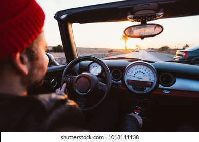Middle age hipster man with beard and small red beanie hat drives convertible cabriolet car with open roof, ready for warm summer days, looks in camera on amazing sunset. Concept lifestyle blogger