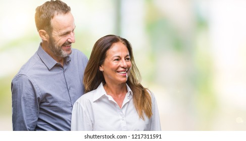 Middle age hispanic business couple over isolated background looking away to side with smile on face, natural expression. Laughing confident.